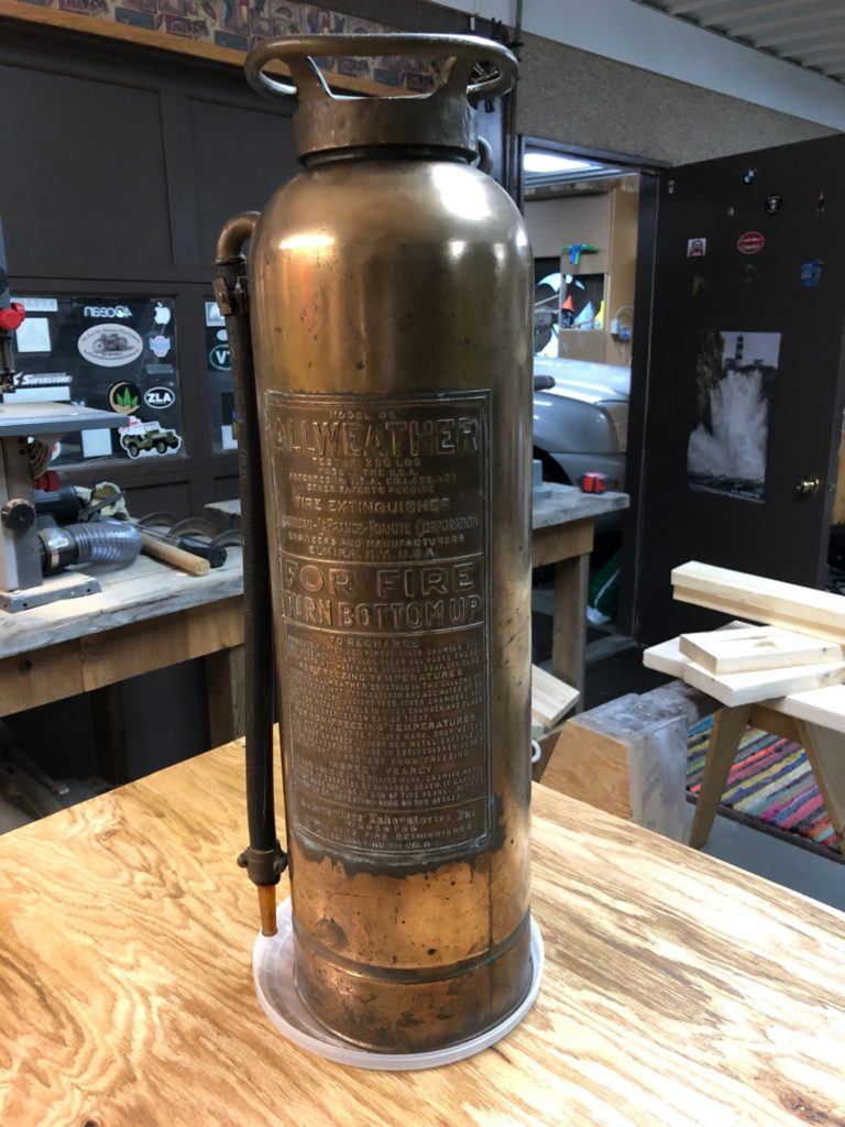 before photo of the brass fire extinguisher was polished and coated with ProtectaClear to prevent tarnish and smudgy fingermarks